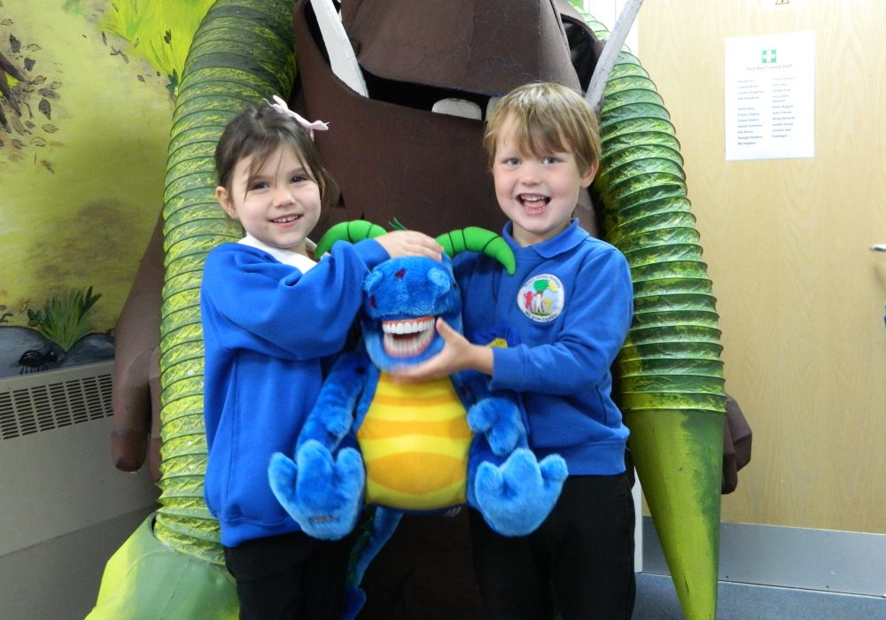 Two schoolchildren holding Brighter Smiles dragon standing with Gruffalo statue